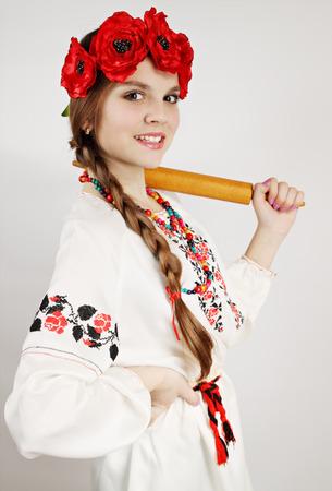 threatens: Ukrainian woman in national costume threatens rolling pin Stock Photo