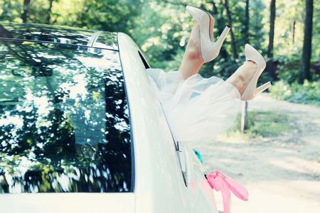 Bride put legs in car window, tinted Archivio Fotografico