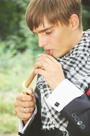 Young handsome guy with a cigar fuming photo
