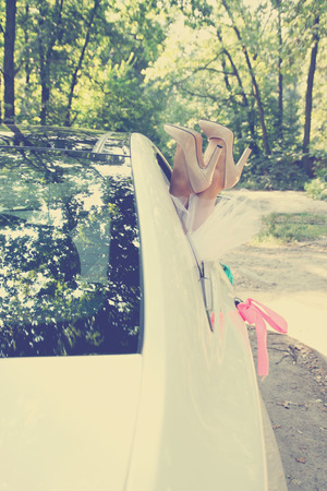 Bride put legs in car window, tinted photo
