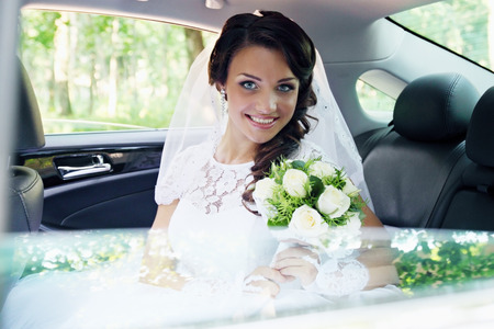beautiful bride with a bouquet of roses sitting in the car photo