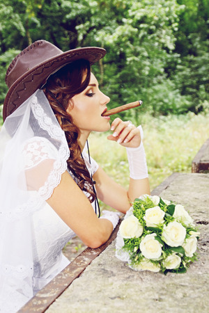 Beautiful bride in a cowboy hat with a cigar Stock Photo