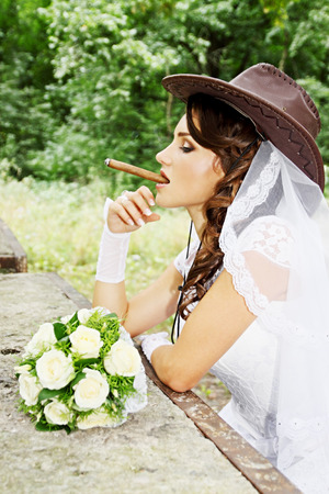 Beautiful bride in a cowboy hat with a cigar photo