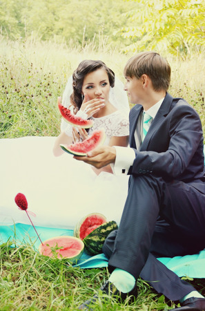 The bride and groom eating watermelon at the picnic photo