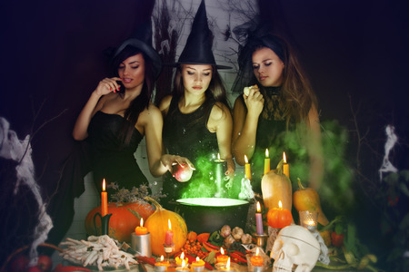 Three beautiful witches brew the potion in the boiler