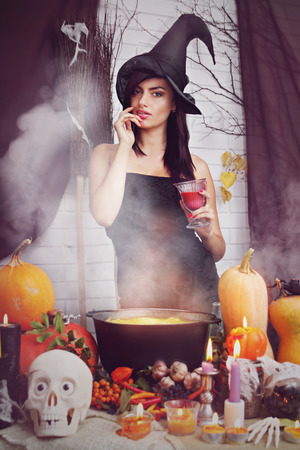 sexy witch with a big glass of blood photo