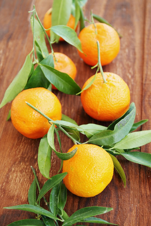 ripe tangerines with leaves on a wooden board photo