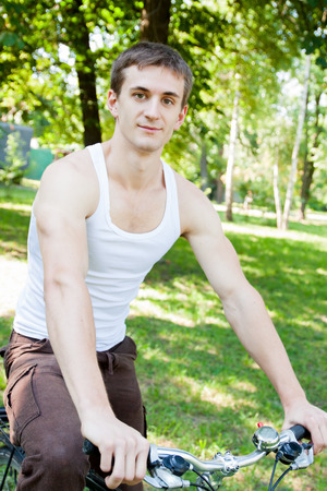 Young beautiful man on a bicycle in the park in the morning  photo