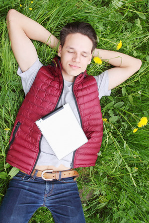 young man lying in the grass with iPads photo