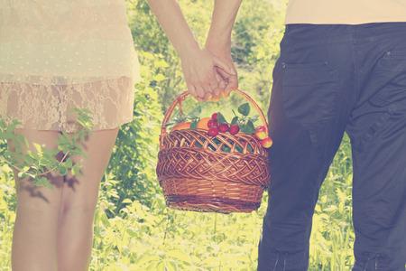 Young couple together bear fruit basket, close-up photo