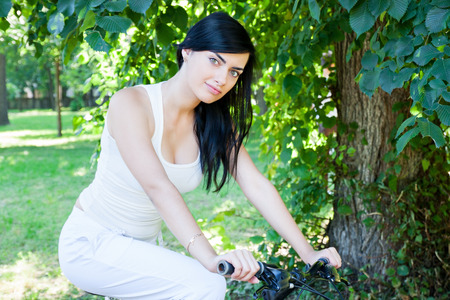 Young beautiful woman on a bicycle in the park in the morning photo
