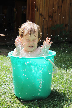 Little girl bathes in a bucket in the yard photo