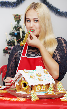 Young beautiful woman decorated gingerbread house photo