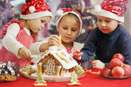 Three kids in caps decorated gingerbread house photo
