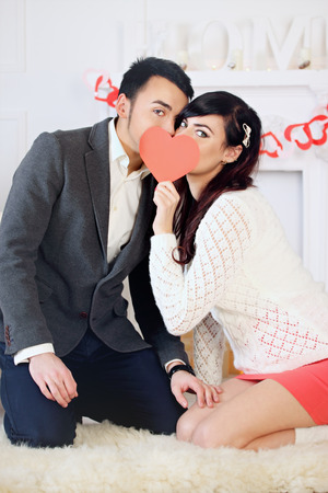 Young beautiful couple kissing with heart in his hands photo