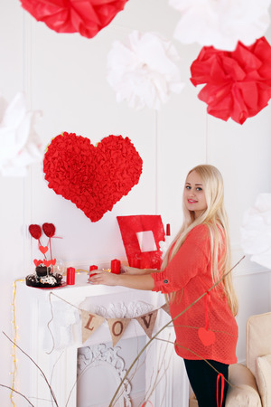 decorates: Woman decorates the house on Valentines Day Stock Photo