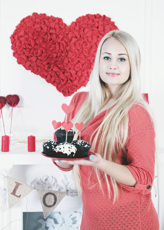 Long-haired blonde holding a festive dessert for Valentines Day photo