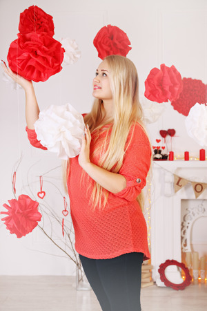 Woman decorates the house on Valentines Day photo