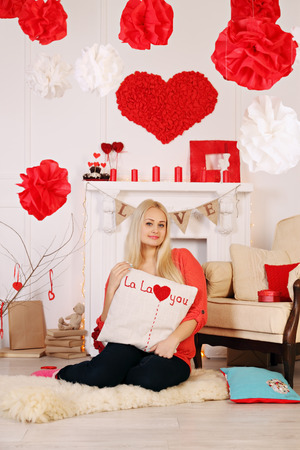 Woman with a pillow by the fireplace in the interior decorations Valentines Day photo