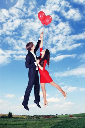 donna volante: l'uomo e la donna in volo su palloncini nel cielo