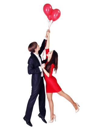 donna volante: uomo e donna in volo su palloncini, sfondo bianco Archivio Fotografico