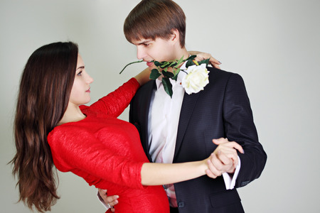 Young beautiful couple dancing tango with a rose photo
