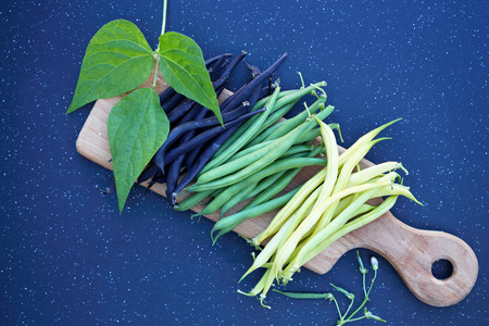 long beans: pods of fresh long beans on a wooden board Stock Photo