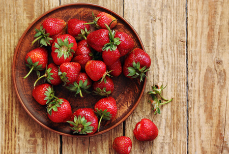 fresh juicy organic strawberries in an old clay bowl