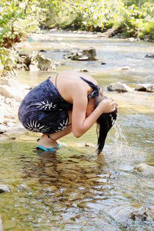 mujeres morenas: Una mujer lava su cabeza en un arroyo de montaña