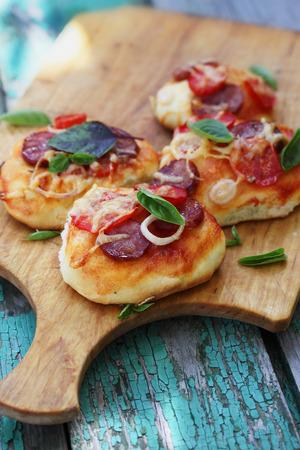 comida chatarra: pequeña pizza hecha en casa en una tabla de madera Foto de archivo