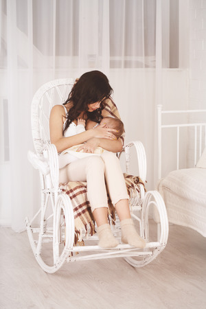 Young mother holding her newborn child. Mom nursing baby. Woman and new born relax in a white bedroom with rocking chair. Family at home. Stock Photo
