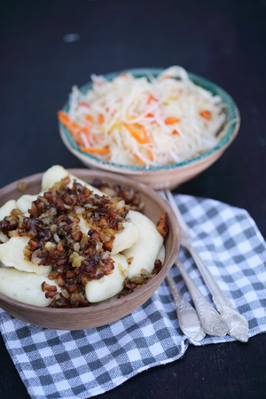 bacon night: vareniki with bacon and coleslaw on a wooden table, top view