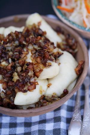 santa cena: Vareniki con tocino y la ensalada de col en una mesa de madera, vista desde arriba
