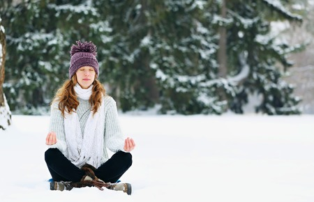 Young woman sitting and meditating at the park in winter Stock Photo