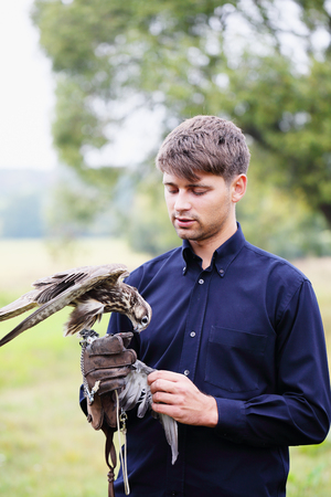 feeds: The owner feeds his falcon dove meat