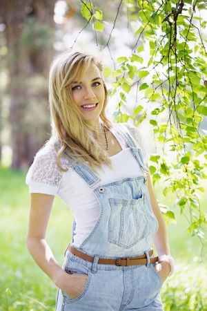 overol: Young beautiful girl in overalls under the birch Foto de archivo