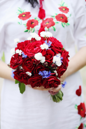 arm bouquet: Wedding bouquet of red roses in the hands of the bride. Wedding in the Ukrainian style
