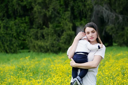tenderly: mother tenderly embracing her child in nature Stock Photo