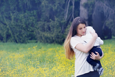 mother tenderly embracing her child in nature Stock Photo