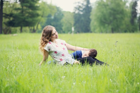 stroked: mother gently stroked her son resting on a meadow
