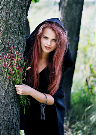 gathers: young beautiful witch gathers herbs for potions