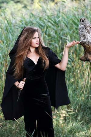 cloak and dagger: young beautiful witch with an owl in the forest, witch holding a dagger