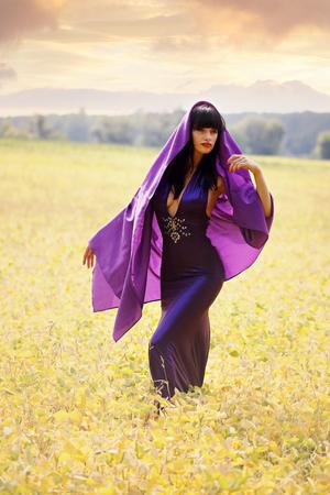 cloak: women in a purple cloak in field Stock Photo
