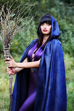 beautiful sexy witch with a broom in the forest Stock Photo