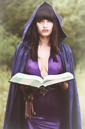 spells: beautiful young witch with with a book of spells