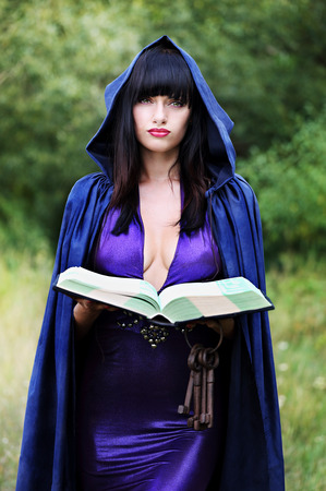 beautiful young witch with with a book of spells