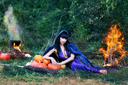 sexy witch near a fire in the forest Stock Photo