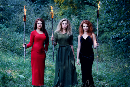 three witches are holding with torches in the forest