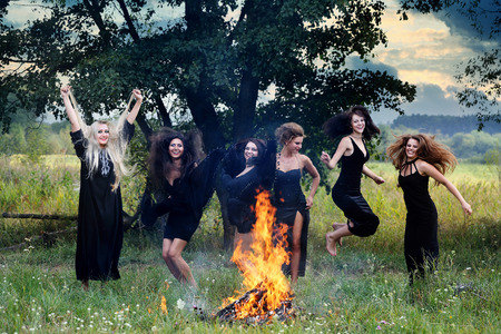 sabbath: witches dancing near a campfire in the meadow