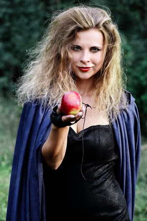 tempt: Young beautiful woman holds out her hand with an apple